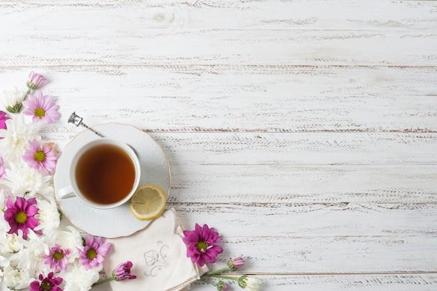 Une vue de dessus de la tasse de thé à base de plantes avec des fleurs sur fond texturé en bois peint Photo gratuit