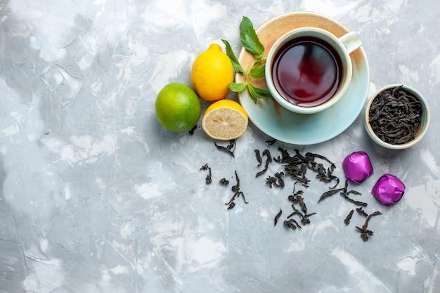 Vue De Dessus Tasse De Thé Avec Des Bonbons De Citrons Frais Et Thé Séché Sur Table Blanche, Thé Aux Agrumes De Fruits Photo gratuit