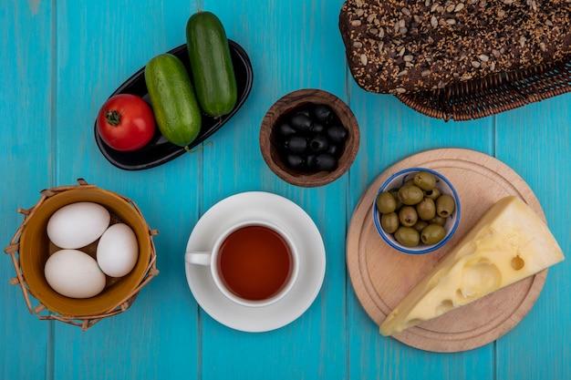 Vue De Dessus Tasse De Thé Avec Concombres Au Fromage Pain Noir Et Tomates Et Olives Avec Des œufs De Poule Sur Fond Turquoise Photo gratuit
