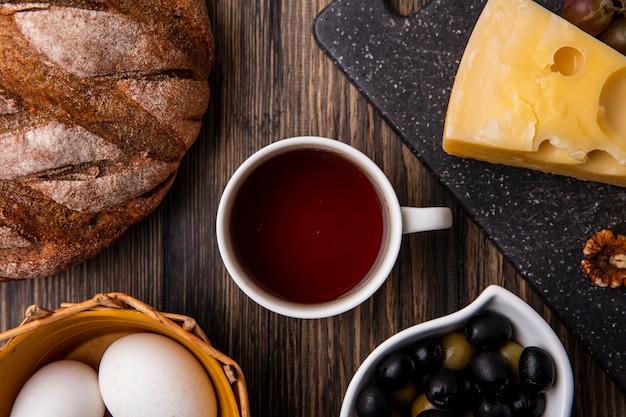 Vue De Dessus Tasse De Thé Avec Du Fromage Maasdam Sur Un Support Avec Des Olives Et Du Pain Noir Sur La Table Photo gratuit