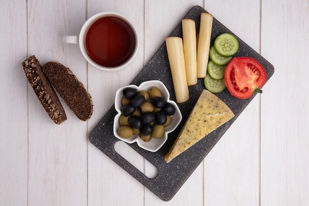 Vue De Dessus Tasse De Thé Avec Des Fromages Fumés Aux Olives Tomate Concombre Et Tranches De Pain Noir Sur Fond Blanc Photo gratuit