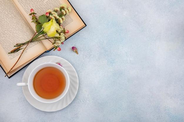 Vue De Dessus D'une Tasse De Thé Avec Rose Jaune Sur Blanc Avec Espace Copie Photo gratuit
