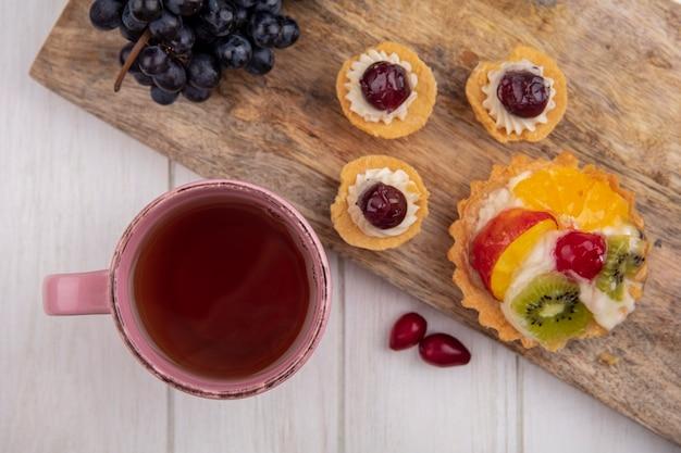 Vue De Dessus Tasse De Thé Avec Tartelettes Et Raisins Noirs Sur Une Planche à Découper Photo gratuit