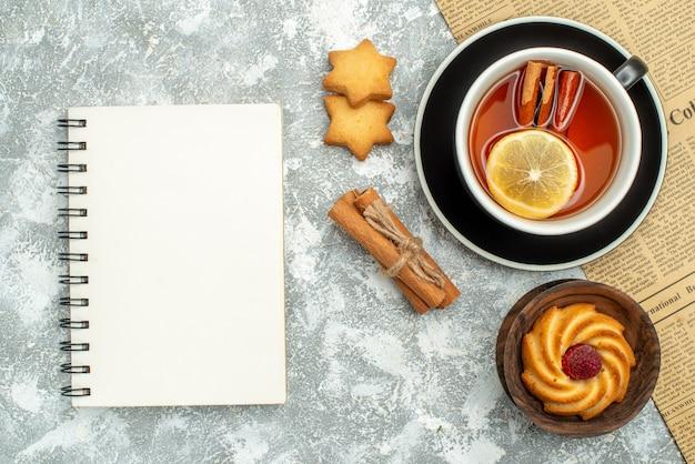 Vue De Dessus Une Tasse De Thé Avec Des Tranches De Citron Et Des Bâtons De Cannelle Sur Les Cookies De Cahier De Journal Sur La Surface Grise Photo gratuit