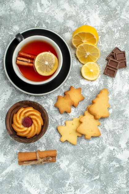 Vue De Dessus Une Tasse De Thé Tranches De Citron Bâtons De Cannelle Cookies Chocolat Sur Surface Grise Photo gratuit