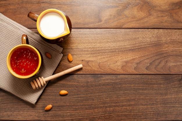 Vue de dessus des tasses de lait et de miel sur la table Photo gratuit