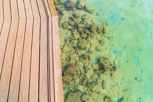 Vue de dessus d'une terrasse en bois sur l'île tropicale des maldives et de la beauté de la mer avec les récifs de corail. Photo Premium