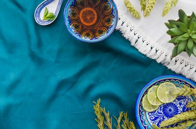 Une vue de dessus de thé au citron à base de plantes avec des ingrédients sur une nappe Photo gratuit