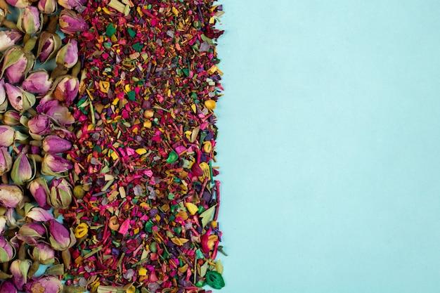 Vue De Dessus Des Tisanes Mixtes Fleurit Des Pétales De Rose Séchées Boutons De Rose Et Des Herbes Sur Bleu Photo gratuit