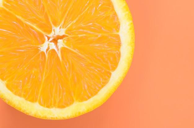 Vue de dessus d'une tranche de fruit orange sur fond clair en couleur orange. une image de texture d'agrumes saturée Photo Premium