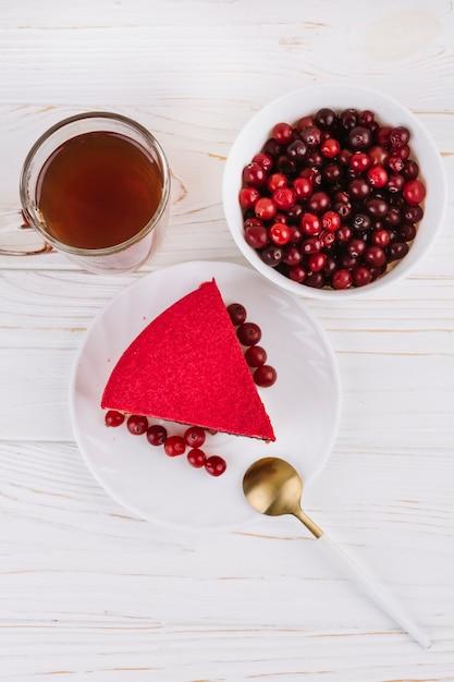 Une vue de dessus de la tranche de gâteau aux baies de cassis rouge sur une plaque blanche sur le fond texturé en bois Photo gratuit