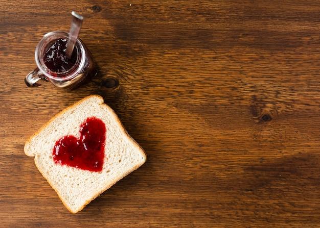 Vue de dessus tranche de pain avec coeur en confiture Photo gratuit
