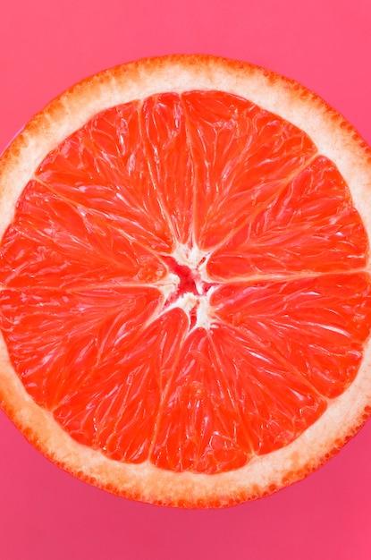 Vue de dessus d'une tranche de pamplemousse sur fond clair en couleur rose pâle Photo Premium