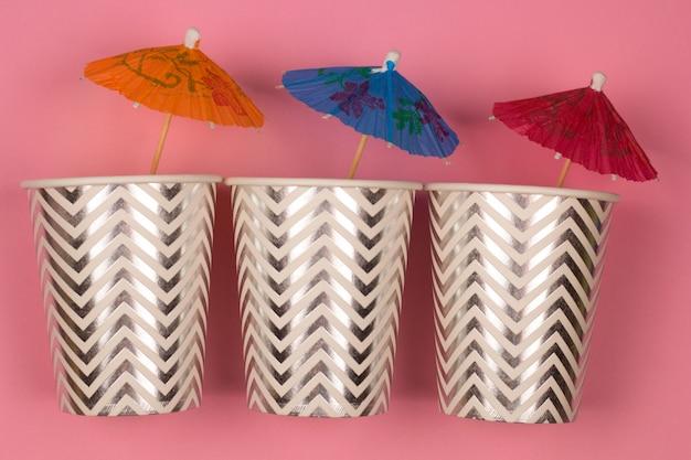 Vue de dessus trois gobelets en papier avec fond rose parapluie cocktail Photo Premium