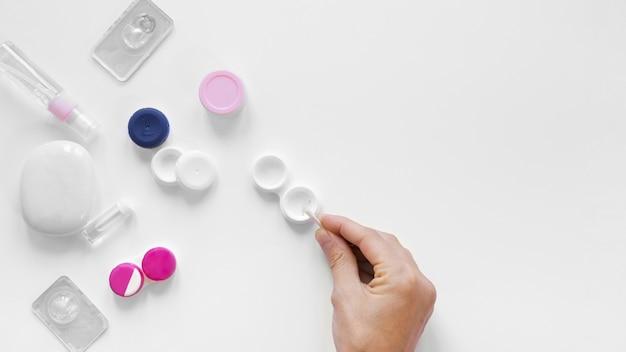 Vue de dessus variété de lentilles et accessoires avec une main Photo gratuit