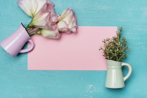 Une vue de dessus de vases en céramique sur papier vierge rose sur fond bleu en bois Photo gratuit