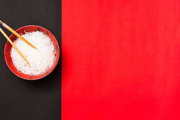 Vue de dessus de vermicelles blancs cuits à la vapeur dans un bol avec des baguettes sur fond double Photo gratuit