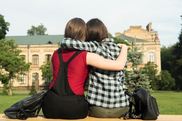 Vue de dos, moyen, de deux adolescentes embrassant Photo gratuit
