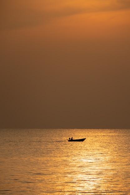 Vue du bateau flottant sur la mer avec le lever du soleil Photo Premium