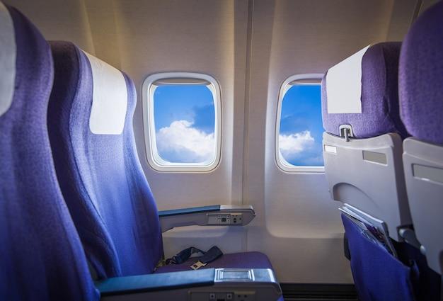 Vue du ciel et des nuages avec la lumière du soleil depuis la fenêtre de l'avion, sièges vides. Photo Premium