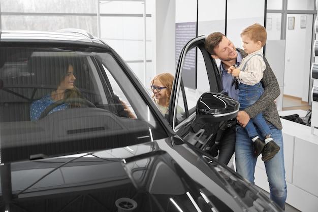 Vue du côté de la famille heureuse, regardant la nouvelle voiture noire dans le salon de l'automobile. Photo Premium