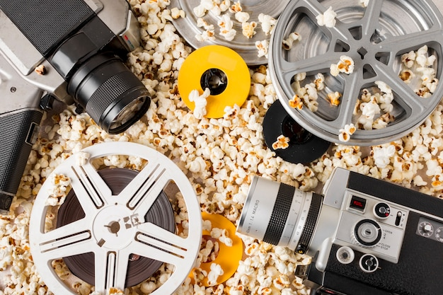 Une vue en élévation de la bobine de film; appareil photo et caméscope sur le pop-corn Photo gratuit