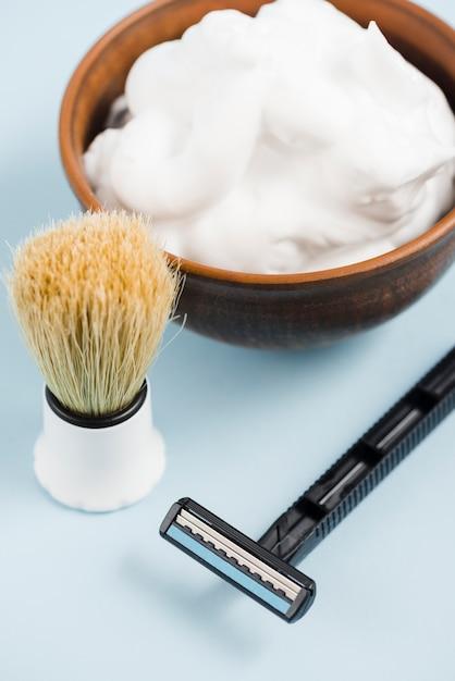 Une vue en élévation du blaireau; rasoir et mousse dans un bol en bois sur fond bleu Photo gratuit