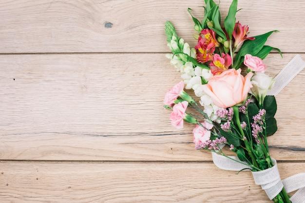 Une vue en élévation du bouquet de fleurs colorées attaché avec un ruban blanc sur un bureau en bois Photo gratuit