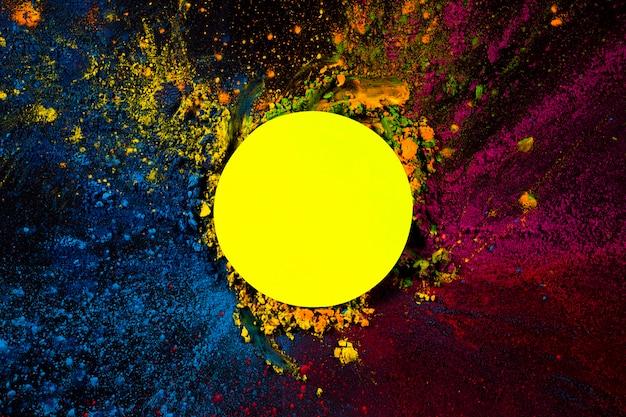 Vue en élévation du cadre circulaire jaune recouvert de couleurs sèches holi Photo gratuit