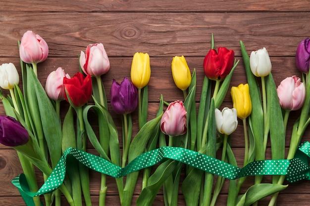 Une vue en élévation du ruban vert sur les tulipes colorées sur une planche texturée en bois Photo gratuit