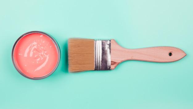 Une vue en élévation du seau de peinture corail et pinceau sur fond de menthe Photo gratuit