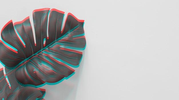 Une vue en élévation de la feuille de monstera avec une lumière rouge et turquoise sur fond blanc Photo gratuit