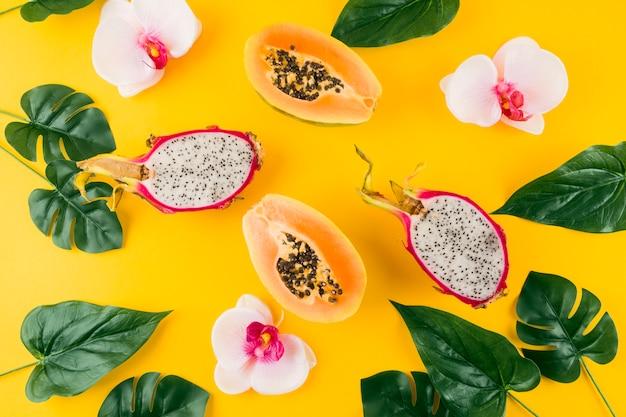 Une vue en élévation de feuilles artificielles avec fleur d'orchidée; dragon et papaye coupés en deux sur fond jaune Photo gratuit
