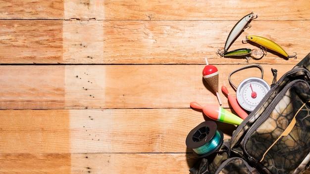 Une vue en élévation des flotteurs de pêche; leurre; bobine et échelle de mesure du sac sur le bureau en bois Photo gratuit