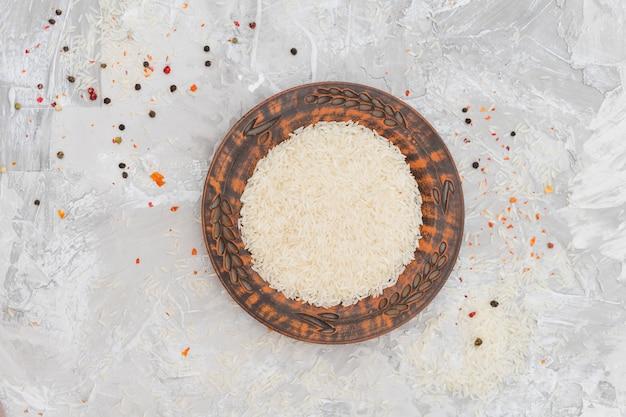 Une vue en élévation de grains de riz sur plaque entourée de grains de poivre rouges et noirs sur fond de béton Photo gratuit