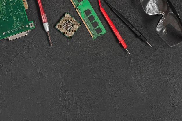 Vue en élévation de pièces d'ordinateur; lunettes de sécurité et multimètre numérique sur fond noir Photo gratuit