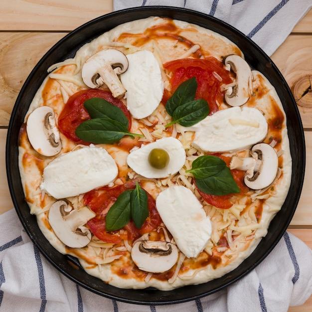 Une vue en élévation de la pizza italienne au fromage; basilic; tomates et olives sur table en bois Photo gratuit