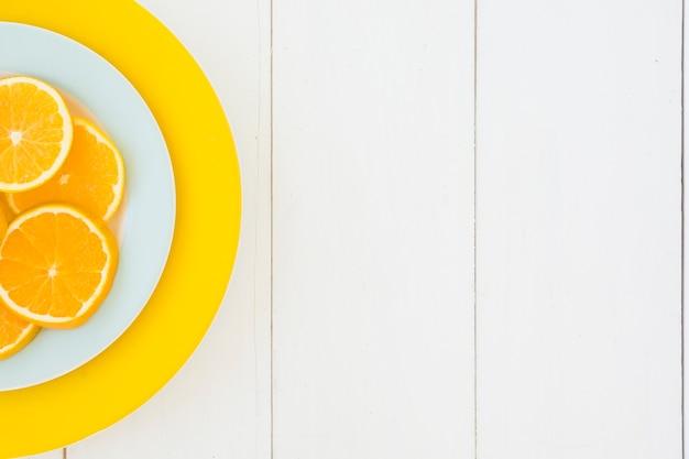 Une vue en élévation d'une tranches d'orange sur des plaques blanches et jaunes sur la planche de bois Photo gratuit