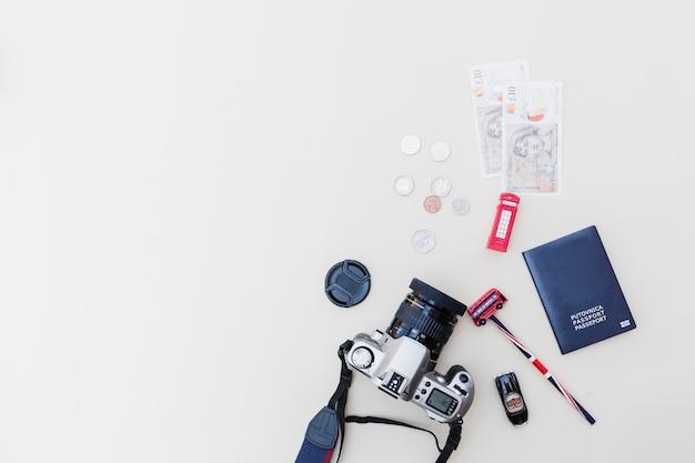 Vue élevée de l'appareil photo reflex numérique, passeport, devises et jouets sur fond clair Photo gratuit