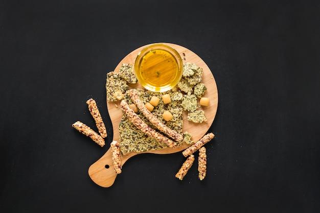 Vue élevée, de, barre granola, à, huile, sur, planche bois, contre, fond noir Photo gratuit