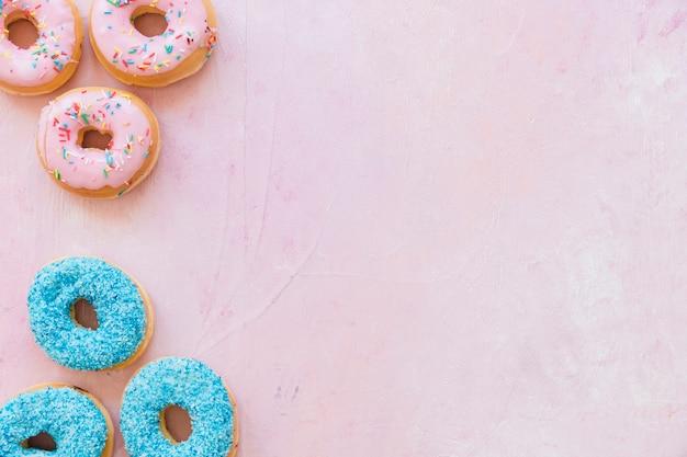 Vue élevée de beignets frais et savoureux sur fond rose Photo gratuit