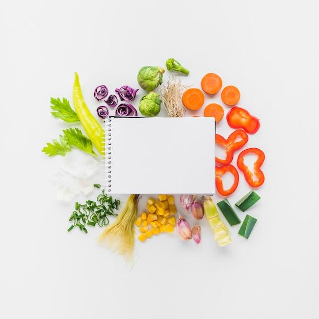 Vue élevée, de, blanc, spirale, bloc-notes, légume frais, sur, fond blanc Photo gratuit