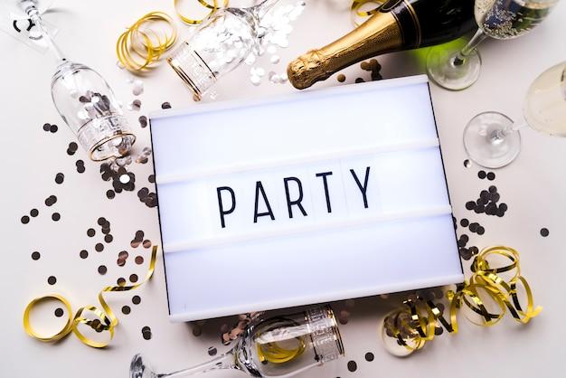 Vue élevée de boîte à lumière de texte de fête et champagne avec des confettis sur fond blanc Photo gratuit