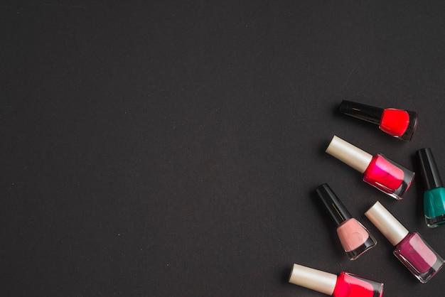 Vue élevée des bouteilles de vernis à ongles sur fond noir Photo gratuit