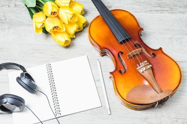 Vue élevée de cahier vierge avec casque; crayon; tulipe et violon classique sur fond de bois Photo gratuit
