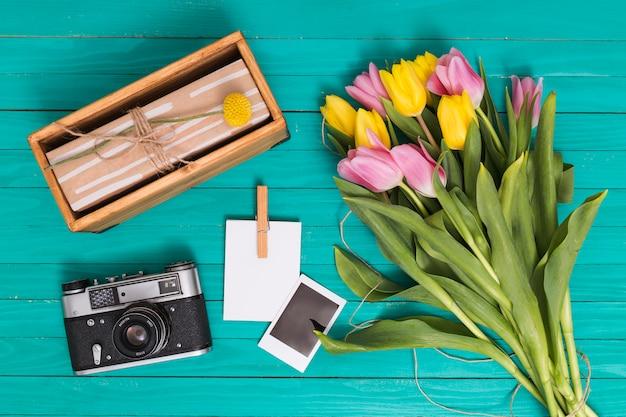Vue élevée De La Caméra Rétro; Boite Cadeau; Copie De Photo; Et Fleurs De Tulipes Sur Fond En Bois Vert Photo gratuit