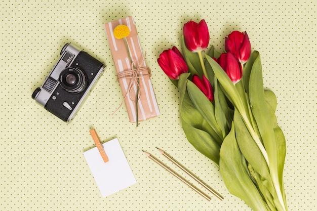 Vue élevée De La Caméra Rétro; Papier Vierge; Des Crayons; Coffret Cadeau Et Bouquet De Fleurs De Tulipes Sur Fond Jaune Photo gratuit