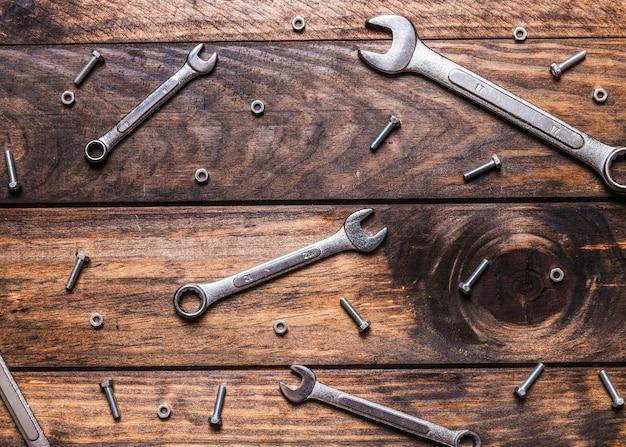 Vue élevée des clés et des vis sur fond en bois Photo gratuit