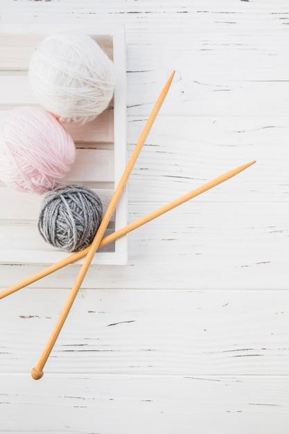Vue élevée, de, coloré, fils, et, crochet, sur, fond bois Photo gratuit