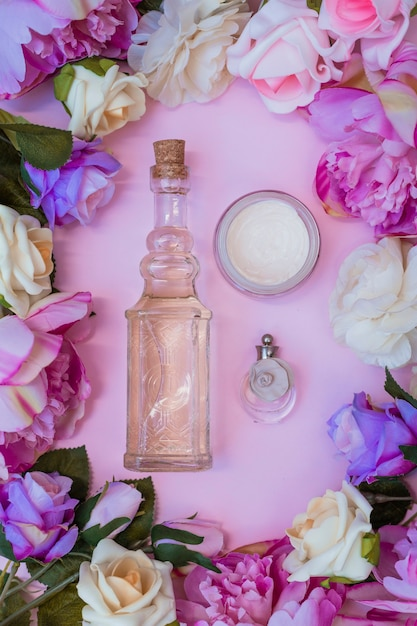 Vue élevée de la crème hydratante; bouteille d'huile essentielle et de parfum entourée de fleurs artificielles Photo gratuit